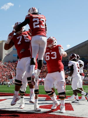 Wisconsin's Dare Ogunbowale (23) celebrates his touchdown run with teammates Micah Kapoi (75) and Michael Deiter (63) during the first half of an NCAA college football game against Troy, Saturday, in Madison