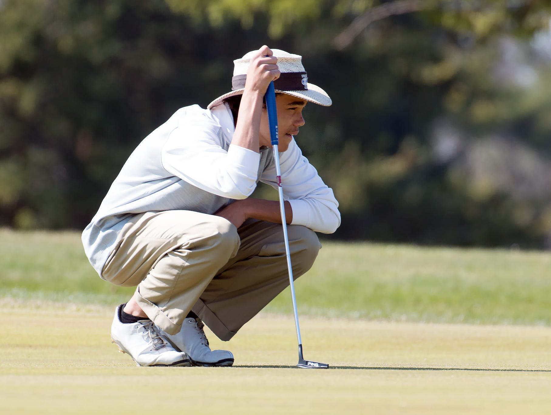 Lakeview's Andrew Walker checks the lay of the green on the 10th hole Thursday afternoon at Cedar Creek golf course.