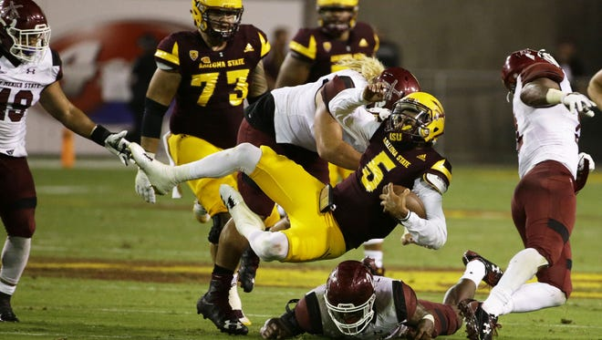 Arizona State quarterback Manny Wilkins is tackled by New Mexico State in the 3rd quarter at Sun Devil Stadium on Thursday, August 31, 2017 in Tempe, Ariz.