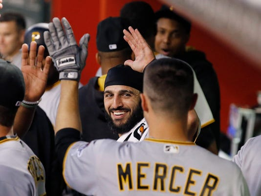Pittsburgh Pirates' Jordy Mercer, right, celebrates his home run against the Arizona Diamondbacks with a smiling Sean Rodriguez, middle, during the third inning of a baseball game Friday, April 22, 2016, in Phoenix. (AP Photo/Ross D. Franklin)