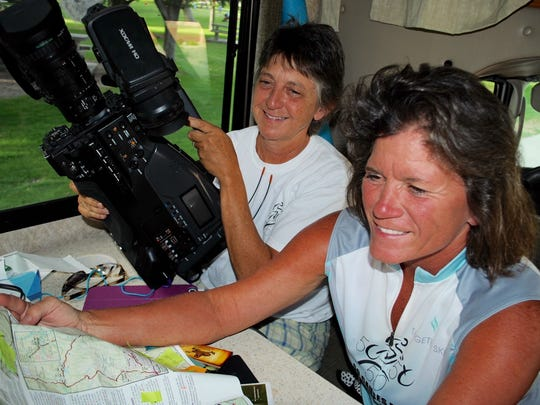 Liz Watkins, left, and Diane Lea prepare multimedia equipment and review maps while sitting in the RV they use in their trip to bring awareness to 50 causes. The duo made a stop in Las Cruces July 7,  2016.