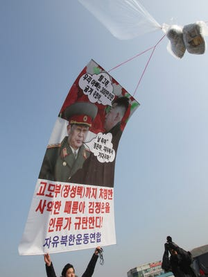 A man holds a banner showing portraits of North Korean leader Kim Jong Un, right, and his late uncle Jang Song Thaek during an anti-North Korea rally in Paju, near the demilitarized zone between the two Koreas, South Korea, on Jan. 15.