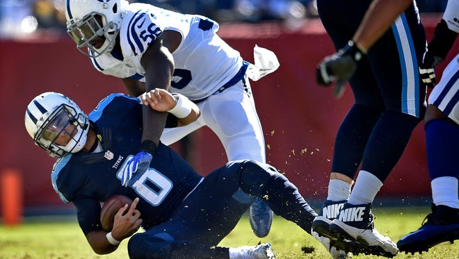 Titans quarterback Marcus Mariota (8) is tackled by Colts linebacker Akeem Ayers (56) in the second half Sunday.