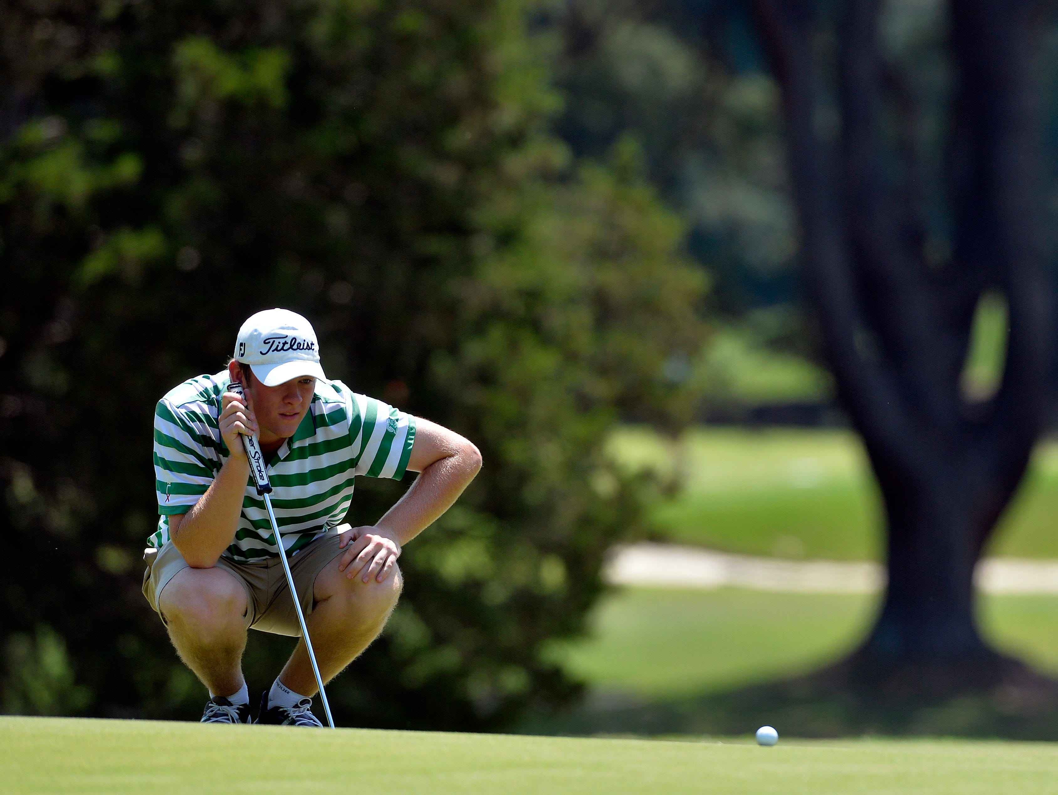 Easley's Matt Carter eyes a putt on the 13th green Monday during the first round of the 77th Kiwanis South Carolina AAAA Golf Tournament at Furman University Golf Course. Carter shot 71 and is two back of the leaders.