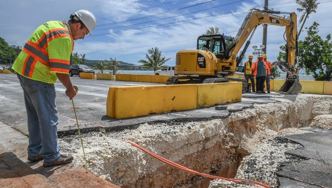 In this file photo, Jeff Wilson, project manager for Parsons Brinckerhoff, takes a measurement needed for a Department of Public Works crew to continue repairs on Route 1 in East Hagåtña.