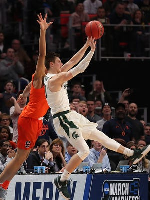 Michigan State's Matt McQuide sinks a three pointer at the half buzzer against Syracuse in the second round of the 2018 NCAA Tournament at Little Caesars Arena in Detroit, Sunday March 18, 2018.