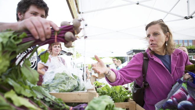Carol Cunningham of Pittsford buys beets from Erik Fellenz of Fellenz Family Farm on opening day of the Brighton Farmers Market last month at Brighton High School.