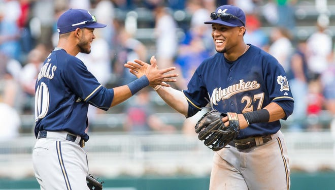 Milwaukee Brewers center fielder Carlos Gomez (27) celebrates the win with shortstop Luis Sardinas (10) after the game against the Minnesota Twins at Target Field. The Milwaukee Brewers beat the Minnesota Twins 4-2.