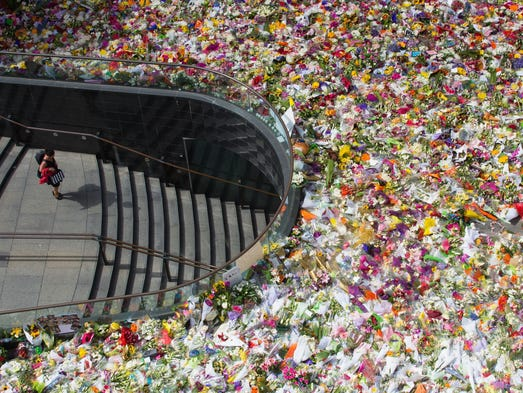A person walks under the flower memorial at Martin