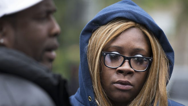 Crystal Davis, the niece of Richard Gregory Davis, listens as her father talks to media at the scene where her uncle died after being Tased by Rochester police.