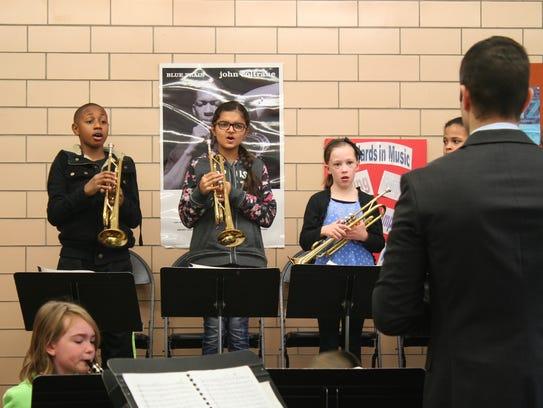 Robert Bickford, 32, rehearses student musicians at