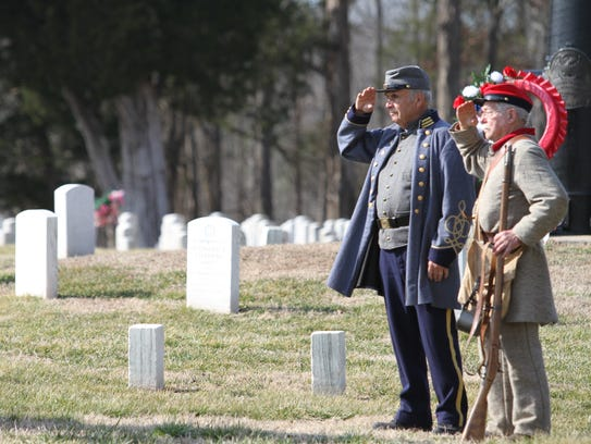 Bob Falkner and George Wallace salute the flag at a