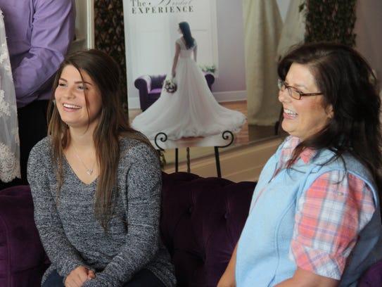 Tori and Kelly Jo Bates look at wedding dresses on