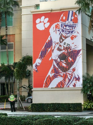 A Tampa policeman stands near a large poster of a Clemson player on the corner of the Marriott Tampa Waterside hotel on Friday during college football national championship week in Tampa, Florida.