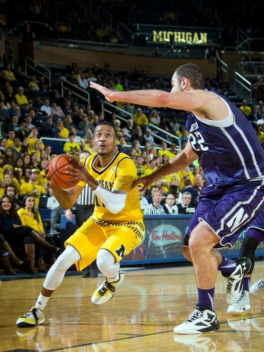 Michigan guard Muhammad-Ali Abdur-Rahkman (12) tries to get to the basket, defended by Northwestern center Alex Olah (22), of Romania, in the second half of an NCAA college basketball game at Crisler Center in Ann Arbor, Mich., Wednesday, Feb. 24, 2016. Michigan won 72-63. (AP Photo/Tony Ding)