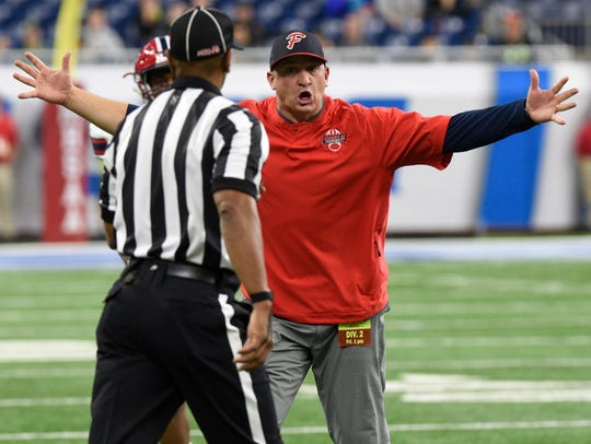 Livonia Franklin head coach Chris Kelbert receives a sideline warning after he argues a non-call during the first half of the Division 2 state championship game against Warren De La Salle on Friday, Nov. 24, at Ford Field.