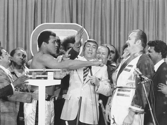 Heavyweight champ Muhammad Ali, left, hams it up with
