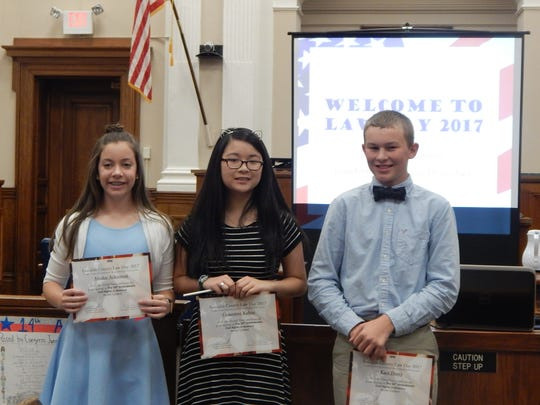 Winners of the Law Day poster contest were, from left, third place Ainslee Ackerman (CAMS North); second place, Genevieve Kuhns (CAMS North); and first place, Kace Dorty (JBMS).