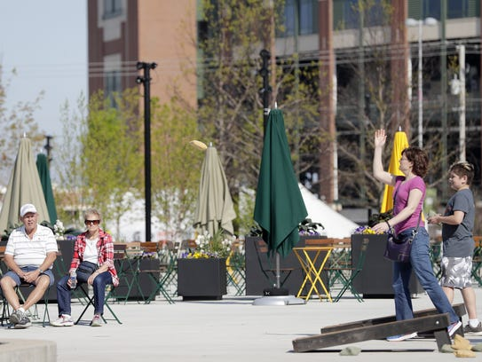 People play a game of bags in the Titletown District