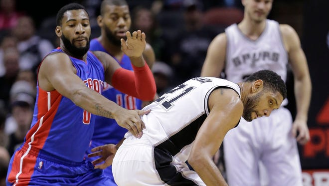 San Antonio Spurs' Tim Duncan loses control of the ball as he is defended by Detroit Pistons' Andre Drummond during the first half.