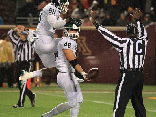 Michigan State Kenny Willekes (48) tosses the ball