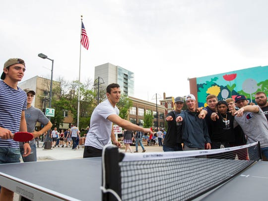 "Iowa wrestlers Paul Glynn (left) and Michael Kemerer play table tennis while teammates look on while calling ""2"" during Iowa CityÕs Downtown Block Party on Saturday, June 23, 2018. The event featured a volleyball tournament, mini golf, a silent disco, live music, and open container alcohol, marking the second year of the annual event."