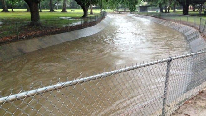 A coulee Oaklawn Park in Lafayette, La., fills quickly after a storm systems dumps 9 inches of rain on the area.