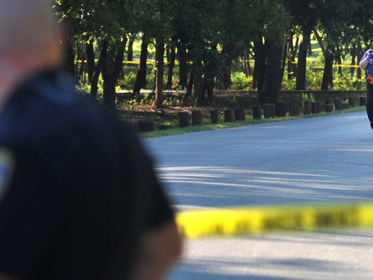 Wichita Falls police gather evidence on Oct. 5, 2016 from the scene of a murder near the entrance to Lucy Park.