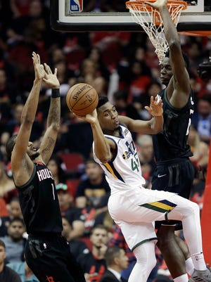 Utah Jazz guard Donovan Mitchell, center, passes the ball as Houston Rockets forward Trevor Ariza, left, and center Clint Capela defend during the first half in Game 5 of an NBA basketball second-round playoff series, Tuesday, May 8, 2018, in Houston. (AP Photo/Eric Christian Smith)