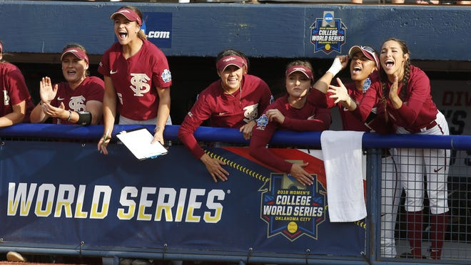 Florida State players cheer in the dugout in the second inning of the first softball game of the best-of-three championship series against Washington in the NCAA Women's College World Series in Oklahoma City, Monday.