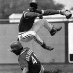 Reds second baseman Bip Roberts leaps out of the way of the Cardinals' Andres Galarraga in March of 1992.
