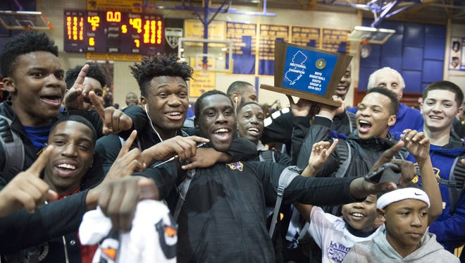 Members of the Camden boys basketball team celebrate with their trophy after winning the South Jersey Group 2 title last year.