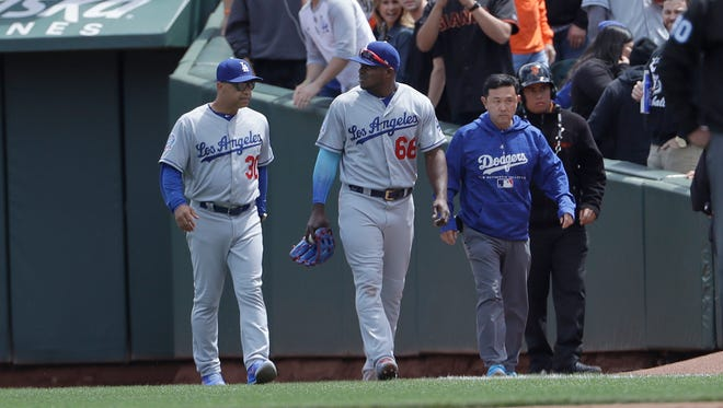 Dodgers outfielder Yasiel Puig, center, walks off the field after injuring his foot making a catch on Friday. He has been put on the disabled list.