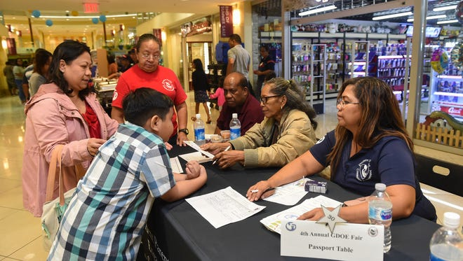 Guam Department of Education employees Rose Mafnas, right, and Trina Palomo, center, assist families at their passport table during the GDOE 2018 Fourth Annual DOE Fair at Agana Shopping Center in Hagåtña, Aug. 4, 2018.