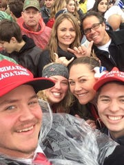 Andrew Gray (front and left) takes a cell phone selfie with friend Justin Dees (front and right) and others in attendance Friday at President Donald J. Trump's inauguration.