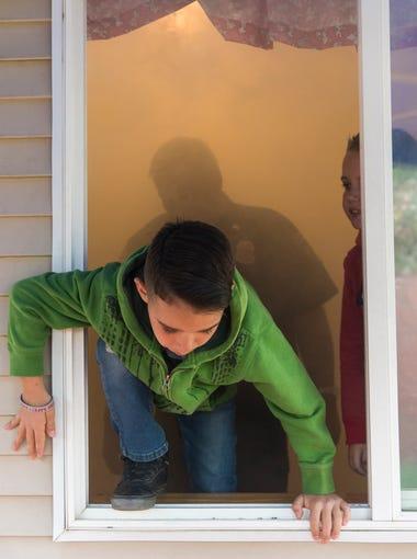 Tiago Guzman, 7, climbs out of a smoky room at the