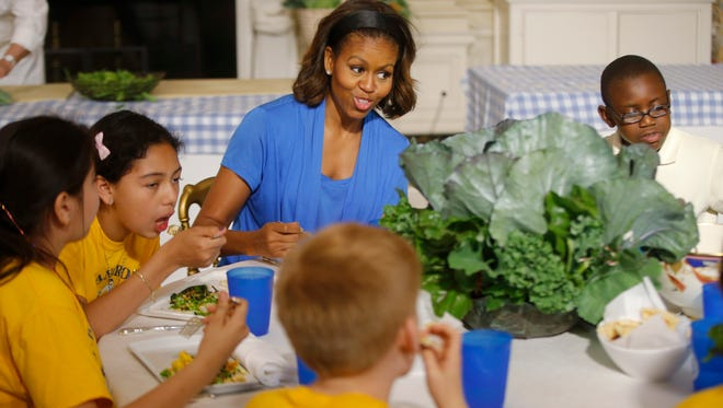 First lady Michelle Obama sits with students to eat salads they made from vegetables harvested from the White House garden Thursday, June 12. Her push for healthy school lunch standards is at the heart of a battle over an agriculture spending bill.