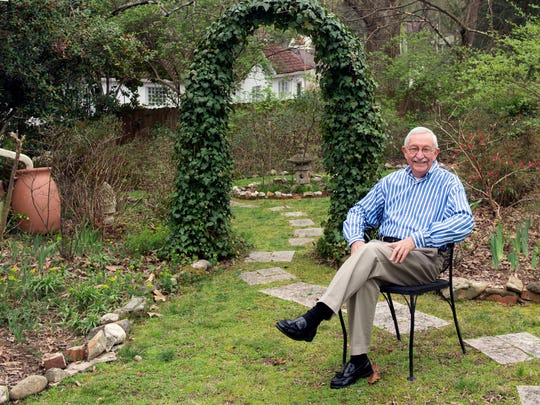 Lloyd King sits in front of the ivy arch in his garden.