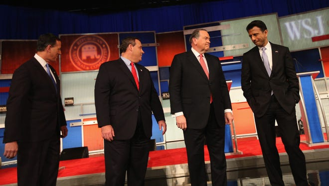 Presidential candidates Rick Santorum, New Jersey Governor Chris Christie, Mike Huckabee, and Louisiana Governor Bobby Jindal take the stage during the Republican Presidential Debate sponsored by Fox Business and the Wall Street Journal at the Milwaukee Theatre November 10.