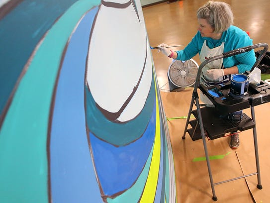 Cynthia Lait works on the mural she is painting inside the Bainbridge Island ferry terminal on Wednesday.