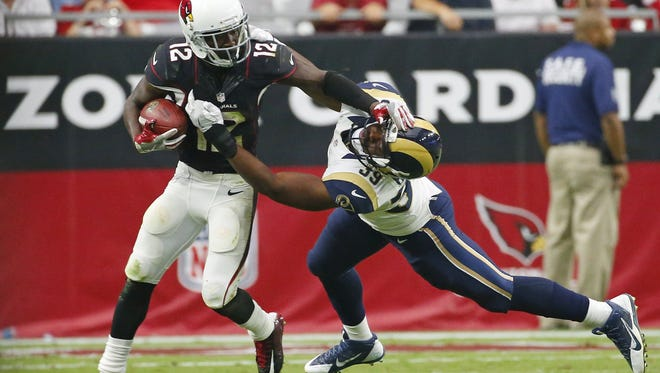 Cardinals wide receiver John Brown (12) stiff-arms Rams running back Malcolm Brown (39) after catch in the fourth quarter at University of Phoenix Stadium October 2, 2016.
