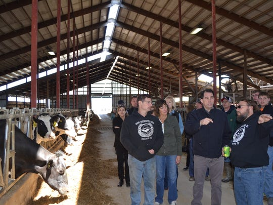Mike Sievert, front right, and Gov. Scott Walker on Wednesday, April 18, 2018, discuss the damage to the dairy barn he and his brother Rod Sievert, front left, operate near Sobieski. Walker and state Secretary of Agriculture Sheila Harsdorf (at Walker's right) along with state FSA executive Sandy Chalmers stopped at two farms to hear from dairy operators in person.