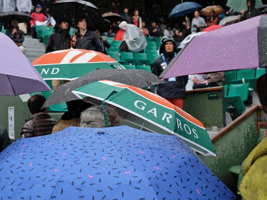 Spectators shield themselves from the rain as the fourth round match of the French Open tennis tournament between Japan's Kei Nishikori and France's Richard Gasquet was interrupted because of the rain at the Roland Garros stadium in Paris, France, Sunday, May 29, 2016. (AP Photo/Alastair Grant)