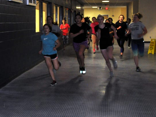 The RHS girls varsity track team races around the gym