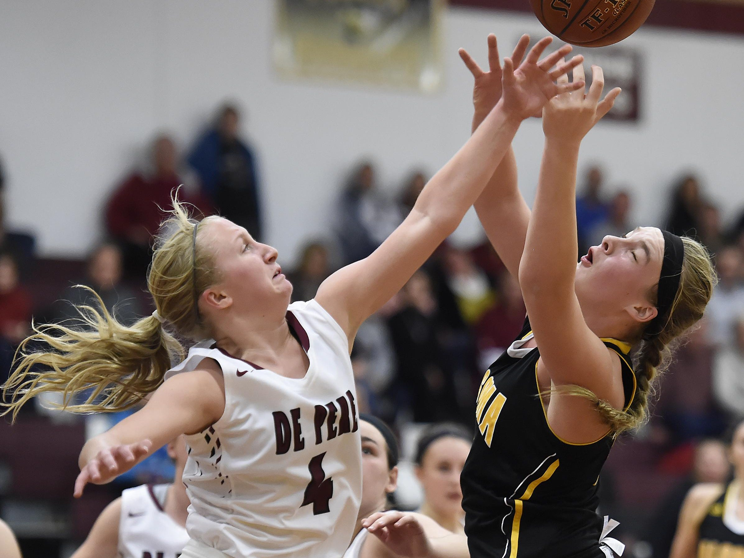 De Pere's Olivia DeCleene (4) and Algoma's Makayla Guilette battle for a rebound in the second half during Tuesday night's girls basketball game at De Pere. See more photos from the game at greenbaypressgazette.com.
