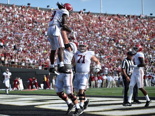 Alabama running back Bo Scarbrough (9) is lifted after