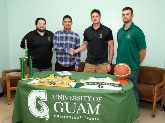 Ryan Nangauta shakes UOG Men's Basketball Head Coach Brent Tipton hand, alongside assistant coaches Josh Torres (left) and Stephen Yates (right).