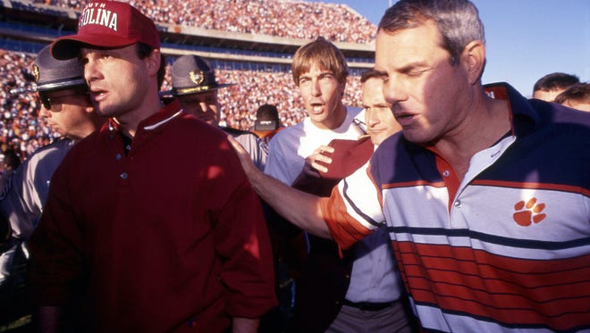 In this 1990 file photo, Clemson head coach Ken Hatfield meets South Carolina head coach Sparky Woods at midfield after Clemson's 24-15 win at Memorial Stadium in Clemson, S.C. [GREENVILLE NEWS FILE PHOTO]