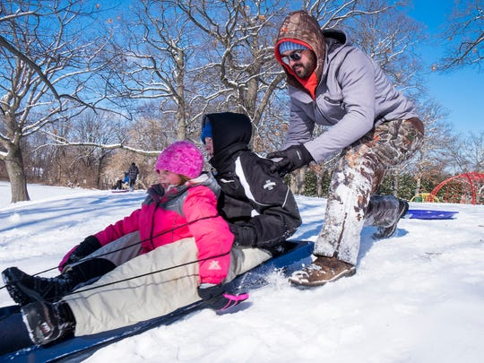Brad Kegebein, of Croswell, right, pushes his kids Kaden, 13 and Keira Hines, 7 down the sleddng hill at the Palmer Park Recreation Center Monday. Kaden and Keira both attend Cros-Lex Community Schools and were given the day off due to snow.