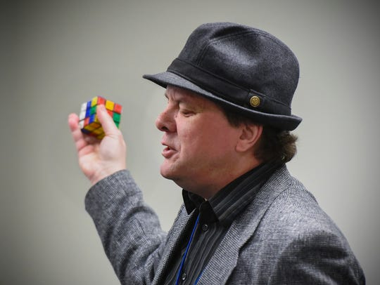 Presenter Wally Wranka shows a Rubik's cube with shapes
